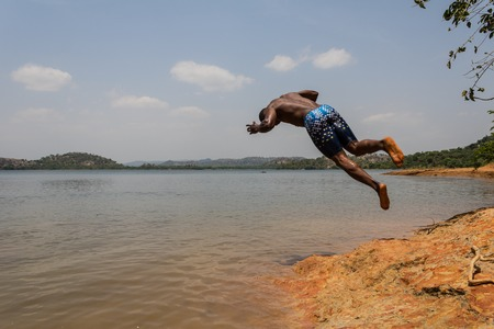 A young muscular athletic man takes a somersault dive into the river in the morning.