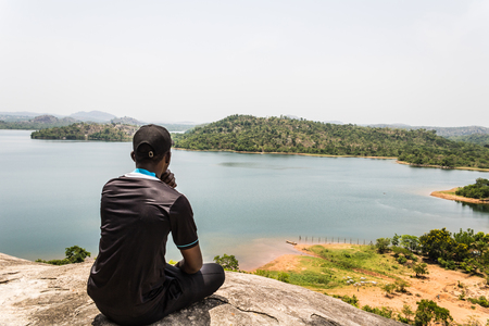 A sport man sitting on top of a mountain and looking ahead at the river and island Stock fotó