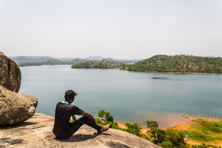 Sitting on an outcropped rock on the top of a mountain looking out towards the lake and island. Stock fotó