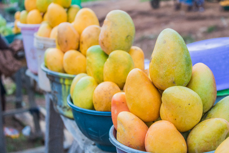 Yellow and green african mango fruits arranged in small portions for sale in a market. Standard-Bild