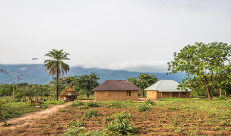 A rural dwelling of villages with a beautiful picturesque cloud capped mountain view in the background.