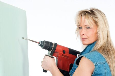 Young blonde woman works with a cordless electric screwdriver photo