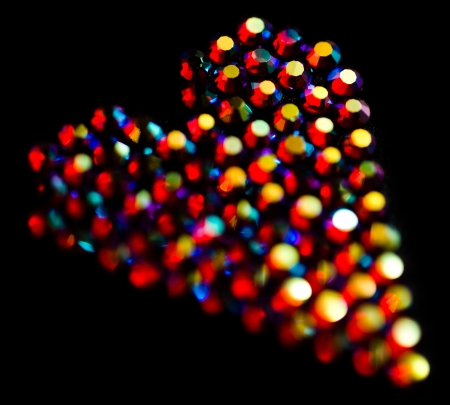 Colorful strass heart pattern on black background photo