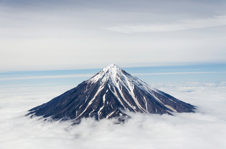 vulcanology: Koryaksky volcano in Kamchatka with the snow peak above the clouds Stock Photo