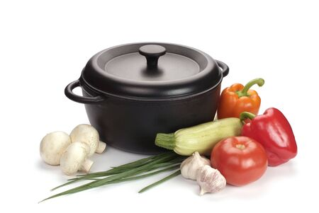 old black cast-iron cauldron with vegetables isolated on white Stock Photo