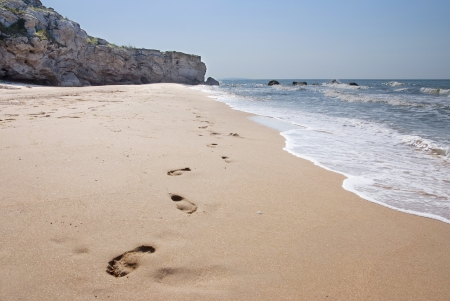 footprints in the sand: deserted beach in summer Crimea