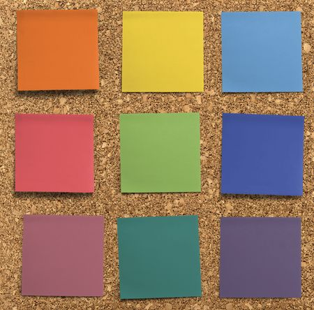 office notes: A set of officework related blank rainbow coloured paper post-it notes. Isolated on cork background.