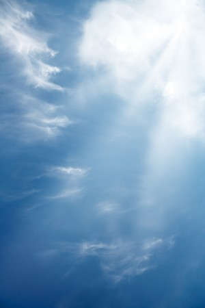 Clouds and a blue sky with a sunrays shining through. photo