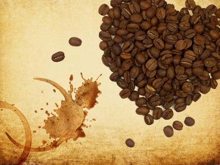 Coffee love concept. Heart shaped coffee beans and coffe rings on vintage paper. photo