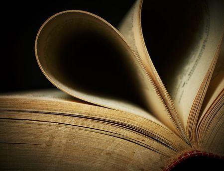 Close-up of abierto viejo libro sobre fondo negro. DOF superficial.  Foto de archivo