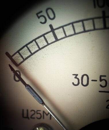 Vintage analog measurement dial with arrow at zero position, closeup. Shallow DOF.