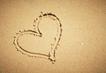 Heart drawn on sand. Horizontal composition. photo