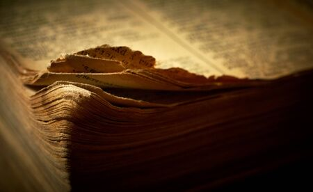 Edge of open old religious book. Shallow DOF. photo