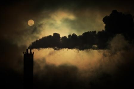 smokestacks: Sun shines through smoke from factory chimneys, telephoto shot  Stock Photo