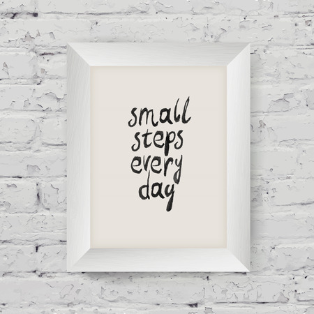 "Motivational poster ""small steps every day"" in the art wooden frame on on white brick wall"