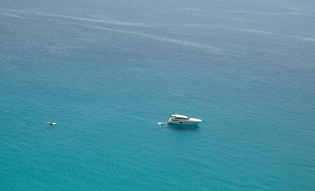 Small boat on the crystal clear sea near the town of Tropea region Calabria - Italy