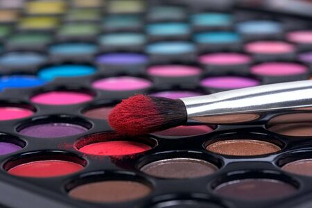 Make-up brush in red shadow on color palette