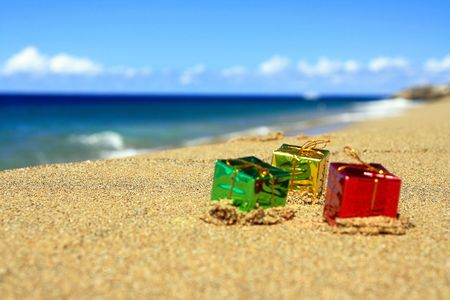 Christmas gift boxes on beach of ocean photo