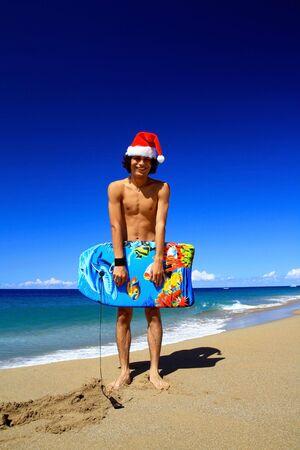 Santa Claus with board on beach of Atlantic ocean photo