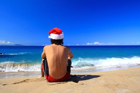 Santa Claus from the back on beach of ocean photo