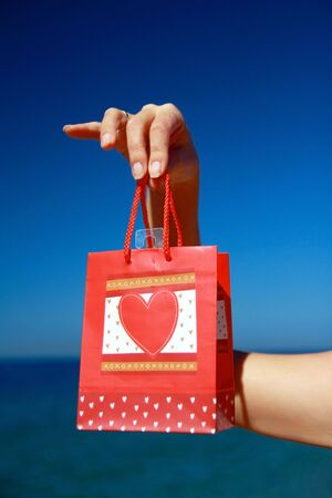 Present with heart in hand on blue sky background photo