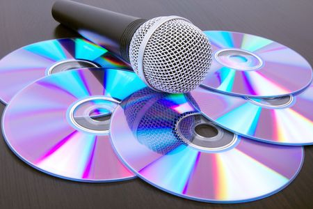 Microphone and dvd disks on black table,closed-up Stock Photo