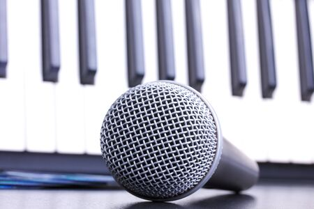 Microphone and piano keyboard on black table,closed-up in studio photo