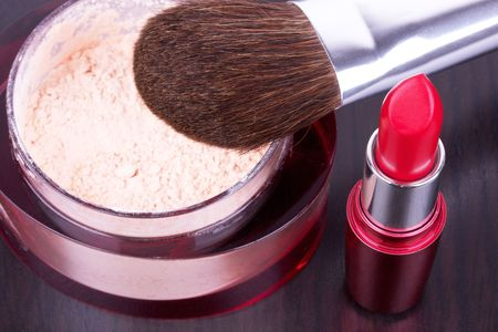 Professional make-up brush on powder and lipstick, closed-up photo