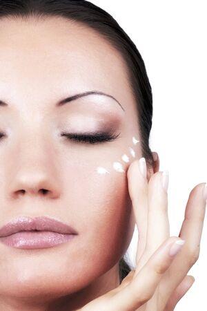 moisturiser: Girl applying cream for eyes area, portrait