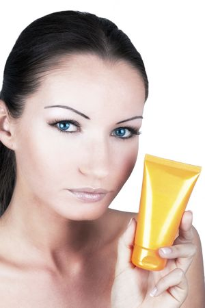 Tanned woman with sun protection cream in her hand photo