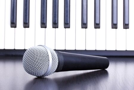 Microphone and piano keyboard in distance,closed-up photo
