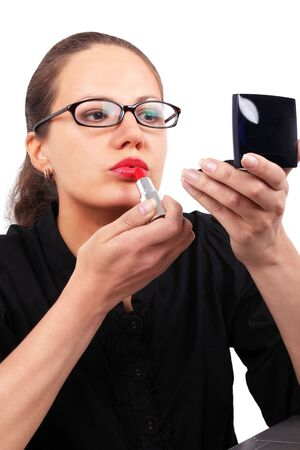Businesswoman in black office blouse looking to mirror using red lipstick photo