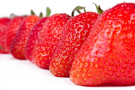 aligned: Strawberries aligned in row, closed-up  on white Stock Photo