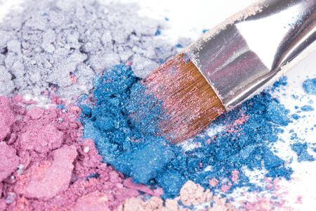 eyemakeup: Professional make-up brush on colour crumbled eyeshadows on white, closed-up Stock Photo