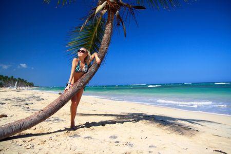 Girl in sunglasses relaxing near a palm, taking suntan  photo