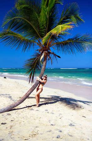 Girl in bikini near palm on caribbean beach  photo