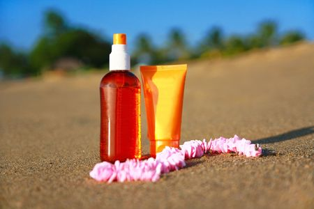 Tubes with sunblock and cockleshell bread on sand on beach Stock Photo - 7943421
