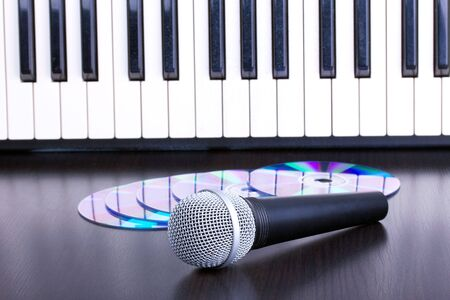 Microphone, cd and piano keyboard on black table,closed-up photo