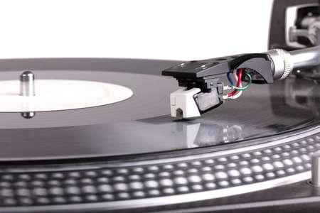 Dj needle on spinning turntable, closed-up on white photo