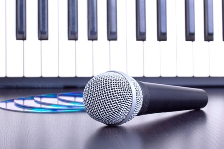 Microphone, cd disks and piano keyboard on black table,closed-up photo
