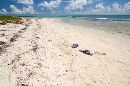 Swim slippers on beach on caribbean sea, Dominican Republic photo