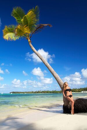 Woman relaxing on palm on a caribbean beach photo