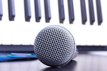 Microphone and piano keyboard on black table,closeup in studio photo