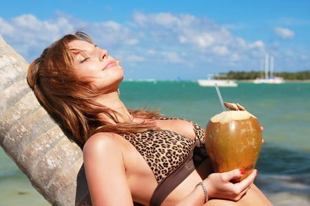 Woman in leopard bikini resting on palm with cocnut in hands photo