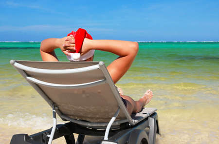 Santa rest on chaise longue on tropical beach, caribbean sea photo