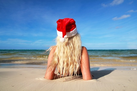 Blond woman in Santa hat on tropical beach photo