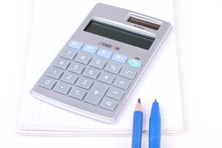 Pen and pencil on notebook and calculator, closeup photo