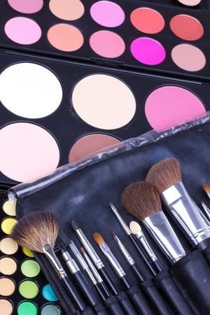 Professional make-up brushes on eyeshadows palettes, closeup photo