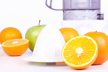 Juicer, oranges and green apple, closeup on white table Stock Photo - 9462474