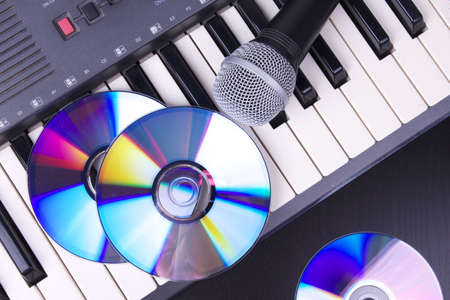 compact disk: Vocal microphone and electronic keyboard, closeup on black table  Stock Photo